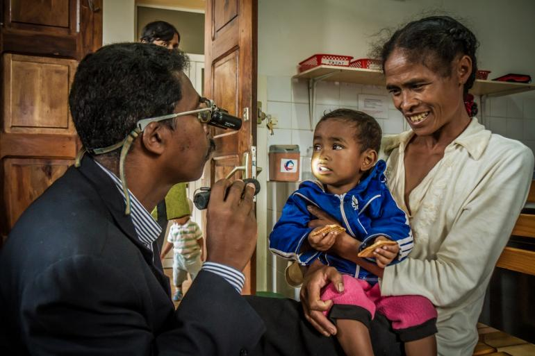 pediatric patient in mother's arms with an ophthamologist who shining light in child's eyes