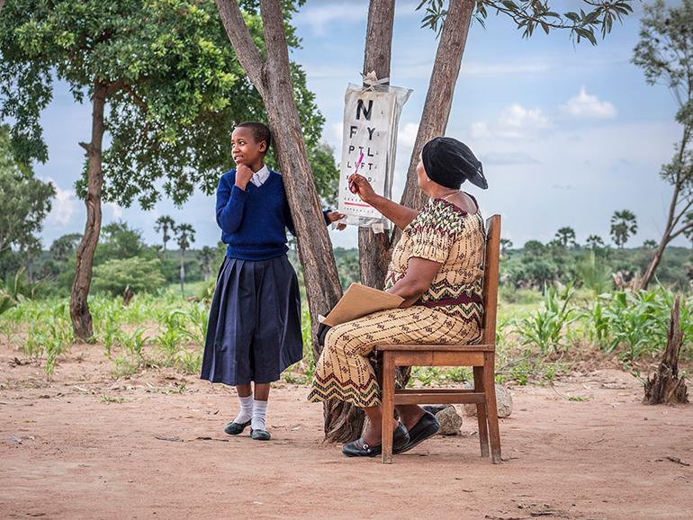 Tanzanian schoolgirl and outreach outreach worker with Echart at a school screening