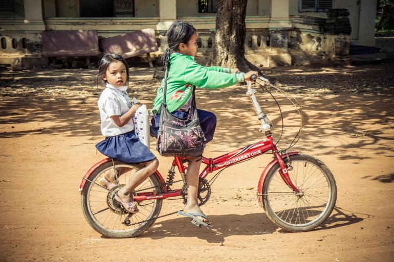 Two young Cambodian girls on a bike
