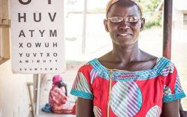 Molly Atim in Uganda standing in front of eye chart