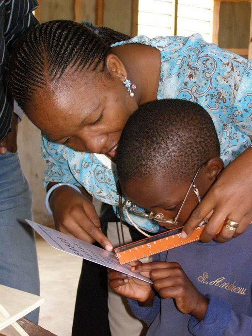 Low Vision Coordinator working with a child with low vision at a school for the blind