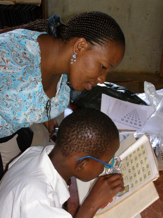 young African boy wearing glasses and reading a book with his mother